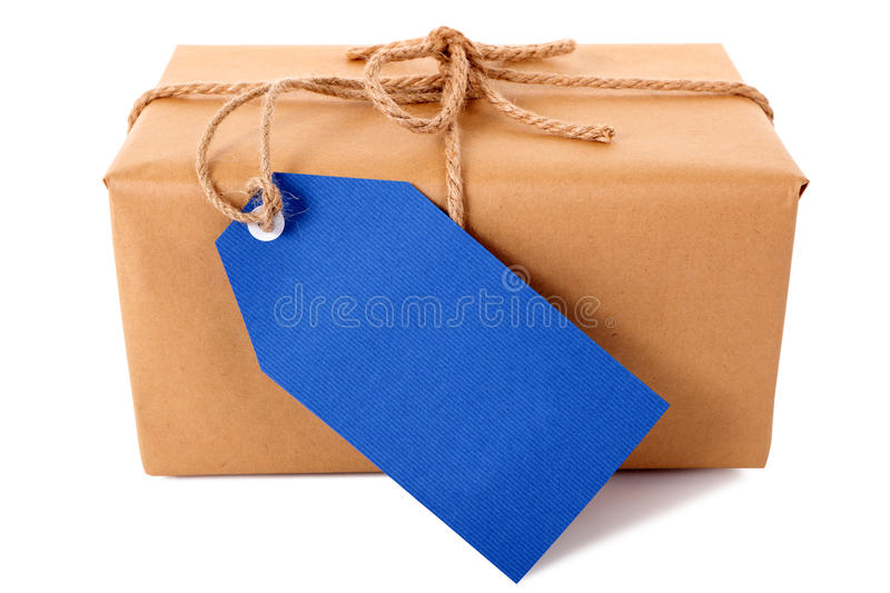 Plain brown paper package or parcel, blue gift tag or address label, isolated, front view. Plain brown paper package or parcel, blue gift tag or label and ribbon royalty free stock photos