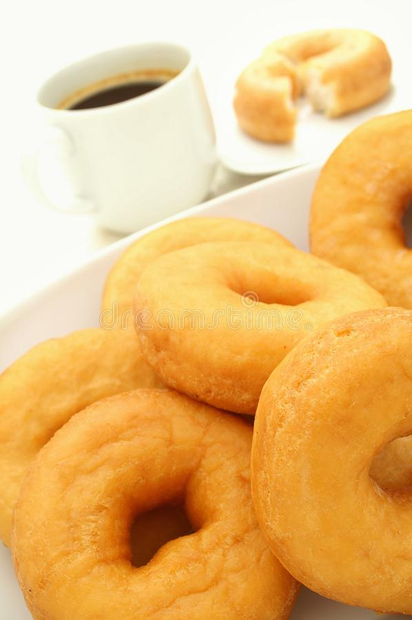 Plain donuts with coffee. Plate of plain donuts with coffee isolated on white background stock image