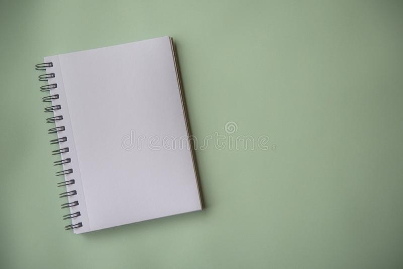Plain empty notebook, on a green background stock photo