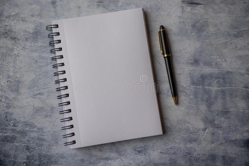 Plain empty notebook with a pen on a blue stone background. Taken with copy space royalty free stock image