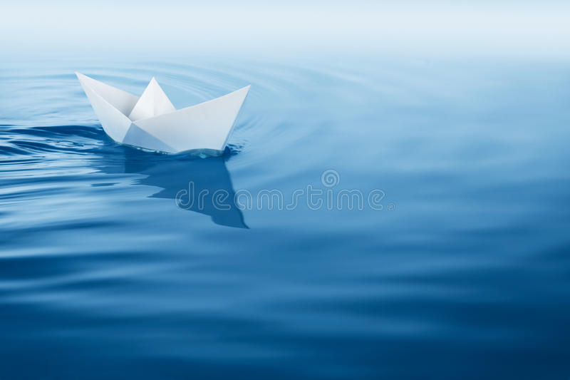 Plain sailing. Paper boat sailing on blue water surface