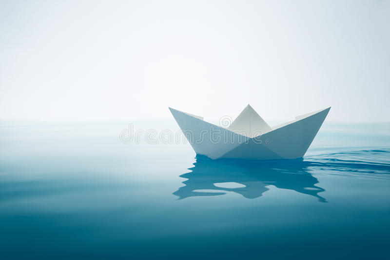 Plain sailing. Paper boat sailing on water with waves and ripples stock image