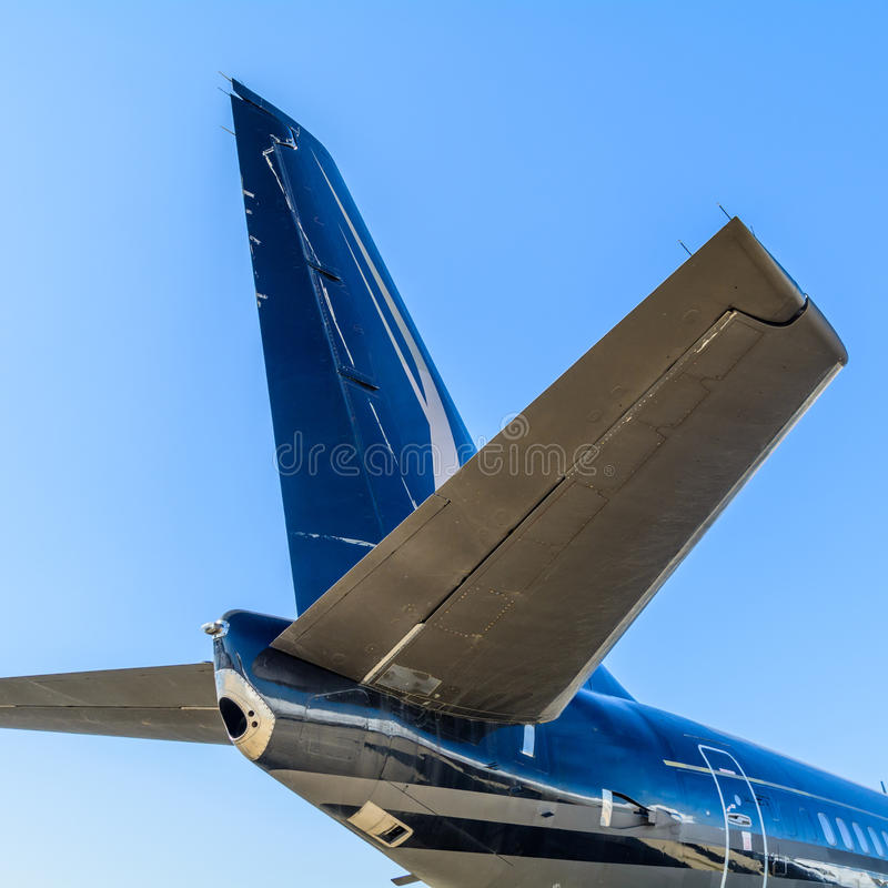 Plain tail over blue sky background. Details of the cargo and c. Ivilian aircraft with no logo on the back of the blue fuselage which is in the air and the sky stock photo