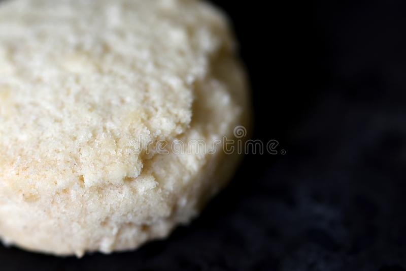 Plain white cookie on black board macro royalty free stock images