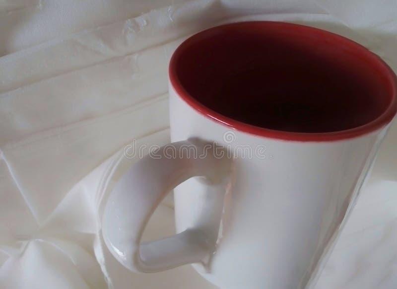 A plain white cup on a textured white cloth stock photos