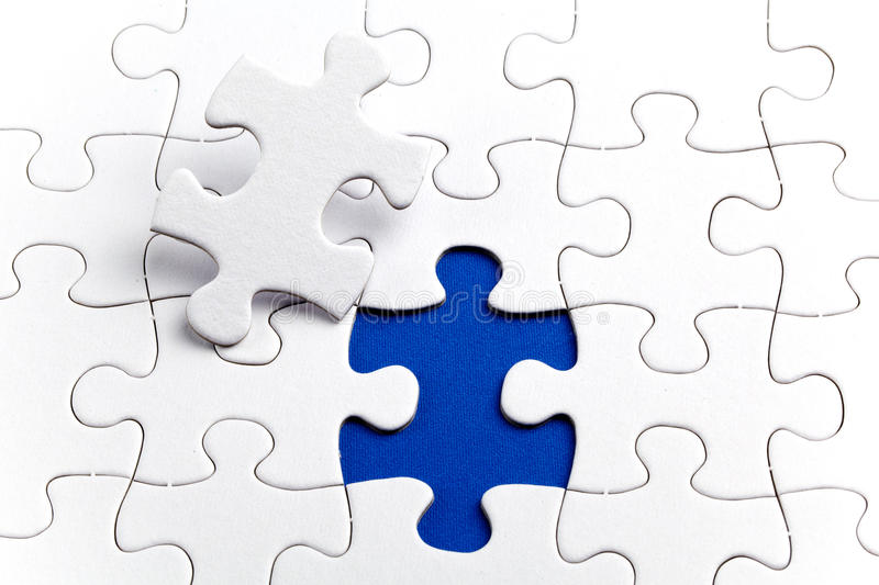 Plain white jigsaw puzzle, on Blue background. Autism awarness symbol royalty free stock photo