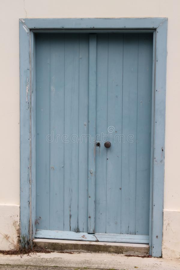 Plain wooden blue door. Plain old double folding blue outside door in a white stone wall royalty free stock photography