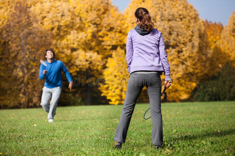 Plaing badminton. Young couple plaing badminton in the park royalty free stock images