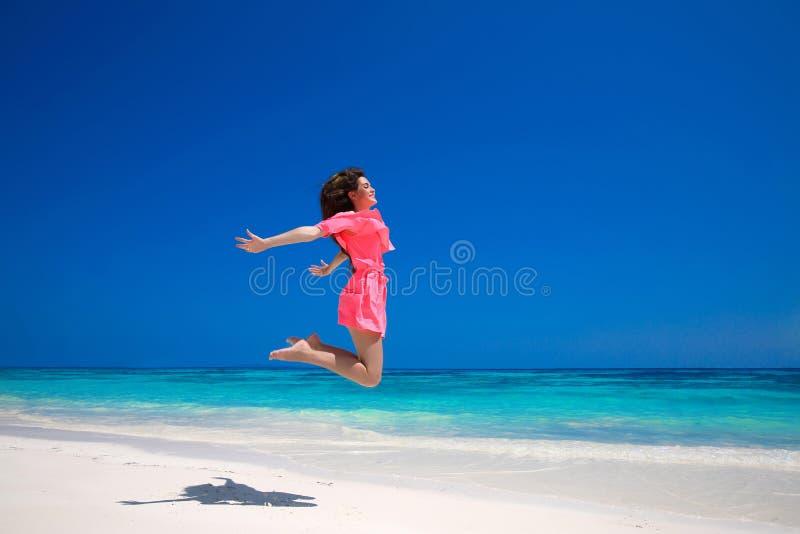 Plaisir d'été Jeune femme heureuse sautant sur la mer, brune image libre de droits