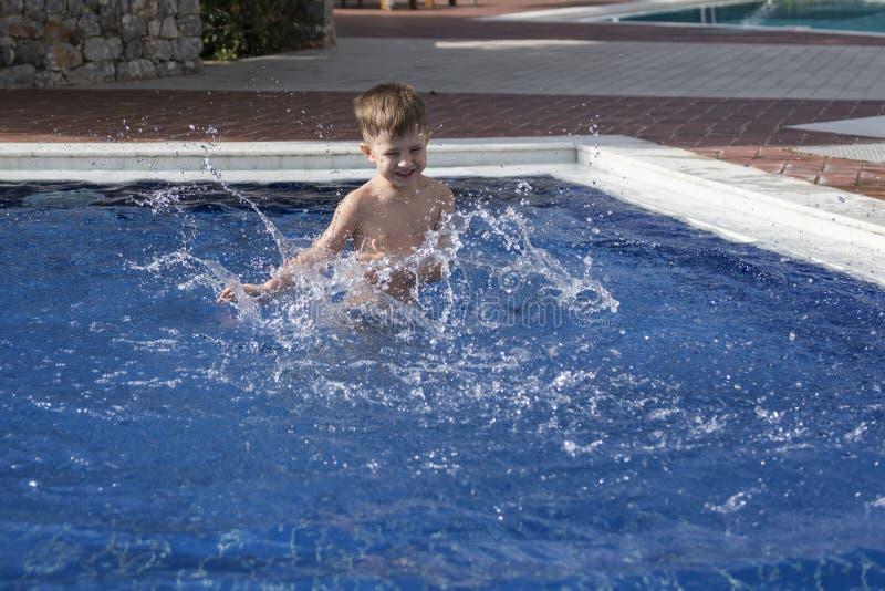 Plaiyng del muchacho en piscina fotos de archivo