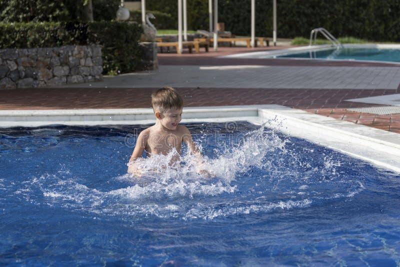 Plaiyng del muchacho en piscina imagenes de archivo