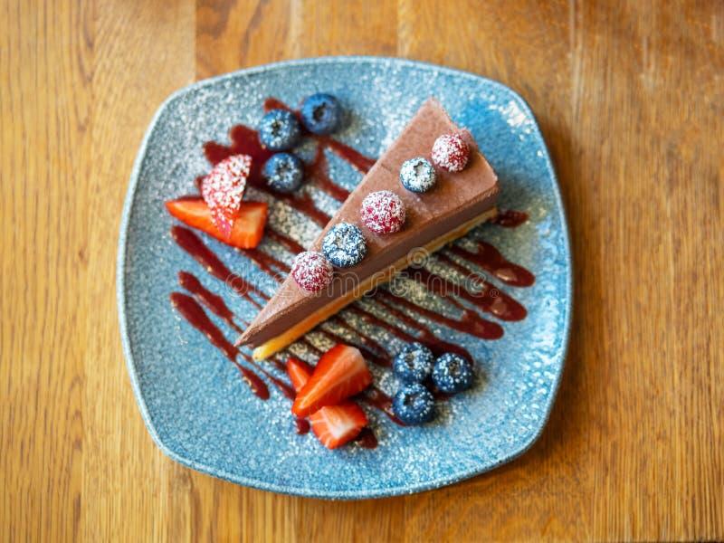 Plak van chocoladekaastaart met aardbeien, bosbessen en frambozen op de blauwe plaat, boven mening over een rustiek hout royalty-vrije stock foto