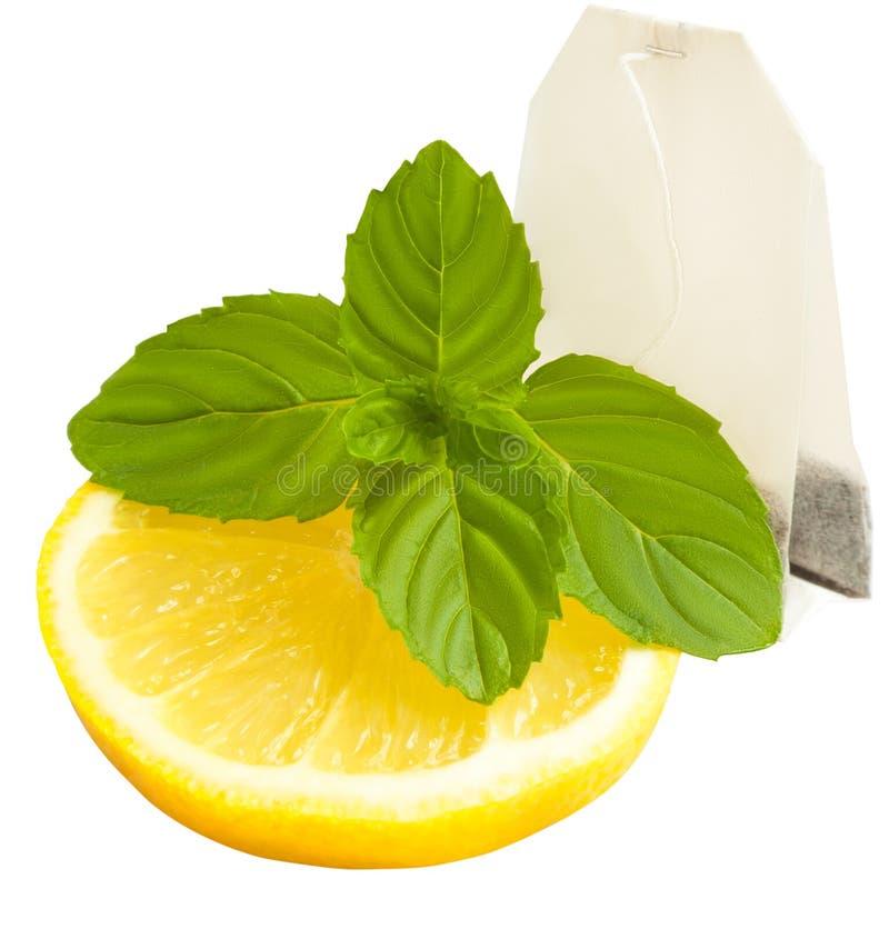 Plak van citroen, munt en theezakje op wit wordt geïsoleerd dat stock fotografie