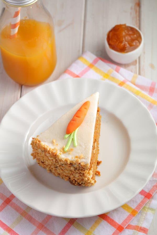 Plak van de Pastelkleur DE zanahoria van de wortelcake met suikerglazuur en marsepeinwortel op witte achtergrond met wortelsap royalty-vrije stock afbeelding