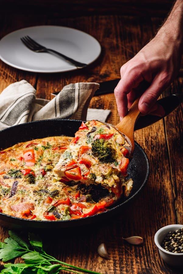 Plak van frittata met broccoli, Spaanse peper en ui stock afbeeldingen