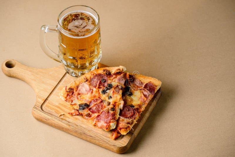 Plak van heerlijke eigengemaakte die pizza met licht koud bier wordt gediend royalty-vrije stock afbeelding