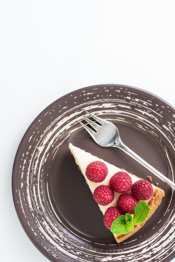 Plak van kaastaart met frambozen op plaat over witte achtergrond, hoogste mening stock fotografie