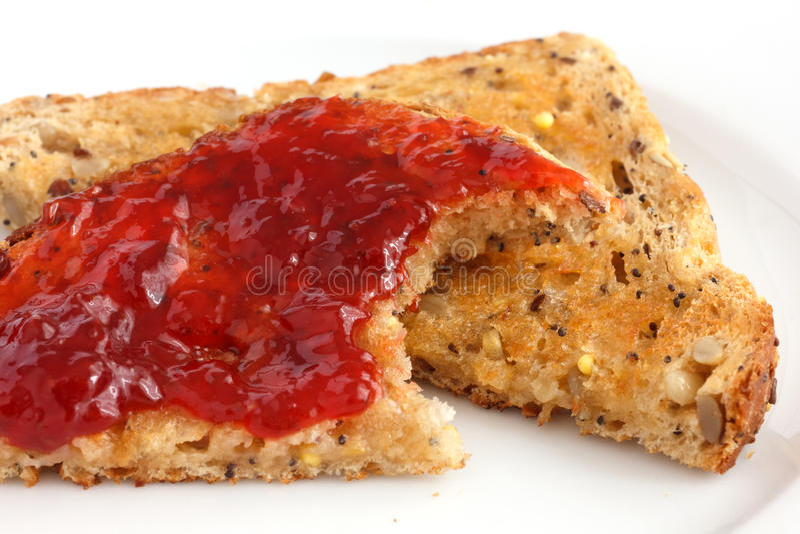 Plak van multi-zaad wholegrain brood en beboterd met jam wordt geroosterd die royalty-vrije stock afbeeldingen
