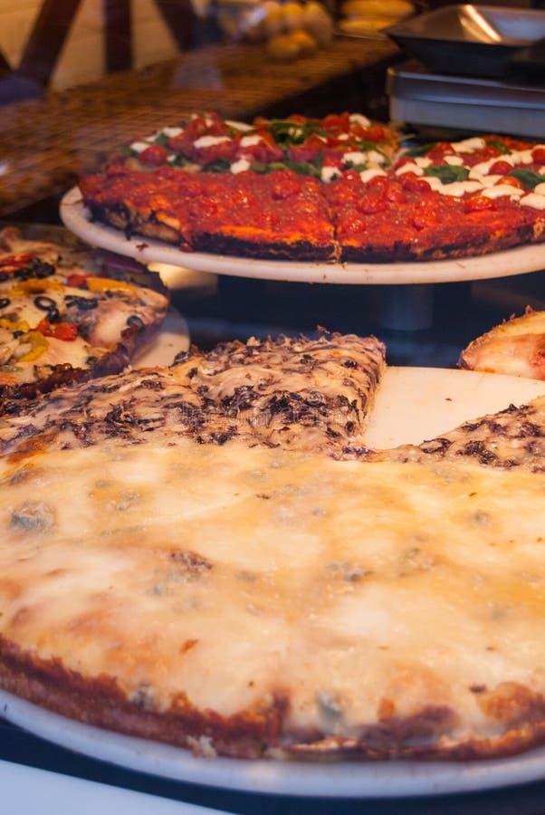 Plak van pizza in een bakkerij wordt blootgesteld die stock afbeelding