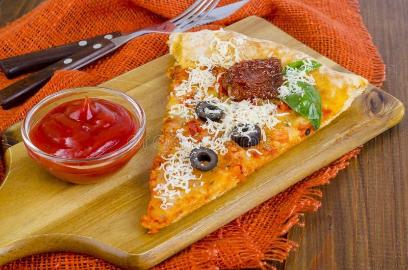 Plak van pizza met droge tomaten, olijven, ketchup op houten lijst royalty-vrije stock afbeeldingen