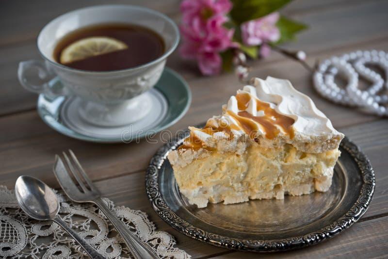 Plak van schuimgebakjecake en een kop thee en bloemen en parels stock afbeelding
