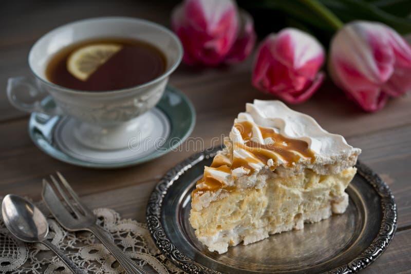 Plak van schuimgebakjecake en een kop thee en tulpen op de lijst royalty-vrije stock foto's