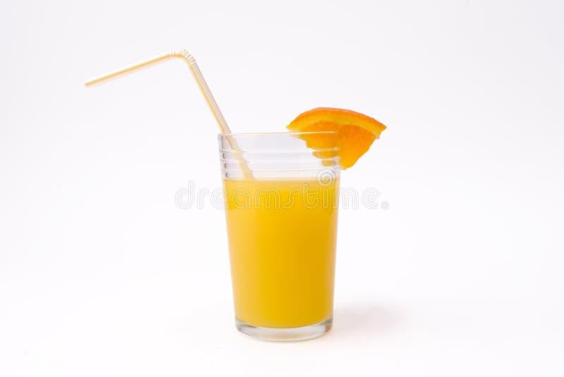 Plak van sinaasappel en glas jus d'orange met stro royalty-vrije stock afbeeldingen