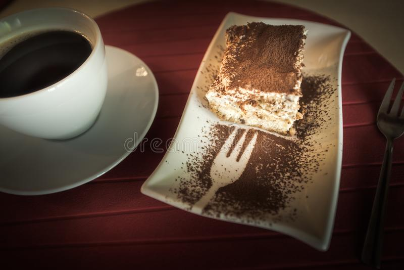 Plak van Tiramisu-Cake en een kop van zwarte koffie stock afbeeldingen