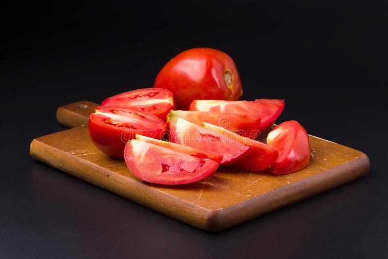 Plak van tomaat die op een zwarte achtergrond wordt geïsoleerd stock afbeeldingen