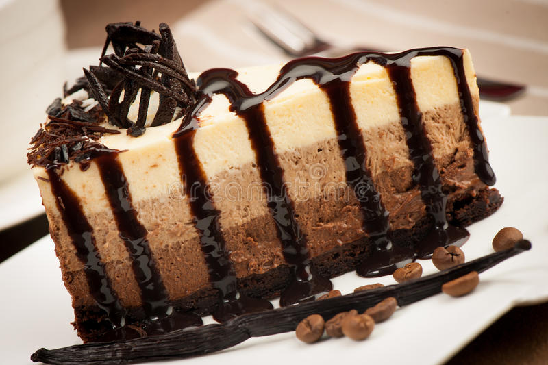 Plak van vanille, chocolade en koffiecake op witte plaat wordt verfraaid die royalty-vrije stock afbeeldingen