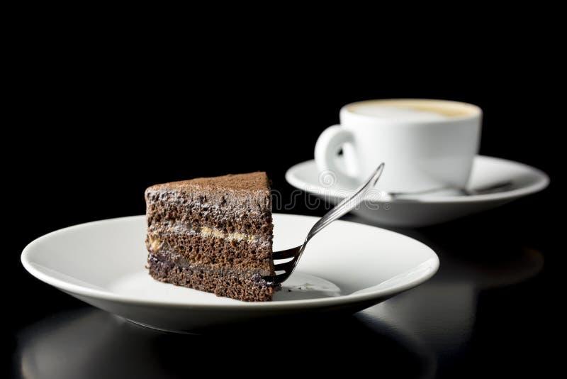 Plak van verse die chocoladecake met koffie wordt gediend stock afbeelding