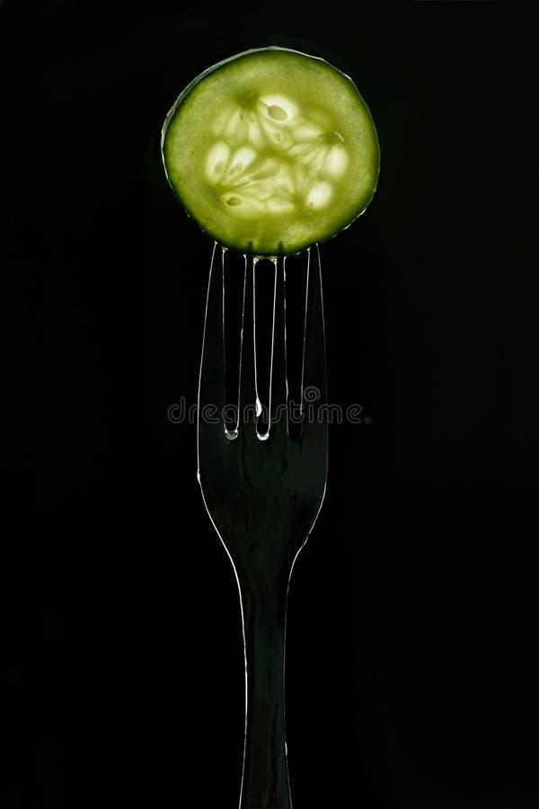 Plak van verse groene komkommer op vork op donkere zwarte achtergrond silhouet van een vork in het achterlicht stock foto's