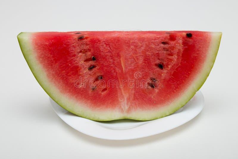 Plak van watermeloen op een plaat witte achtergrond stock foto