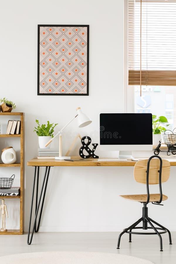 Plakat auf weißer Wand über hölzernem Schreibtisch mit Lampen- und Desktop-COM stockfoto