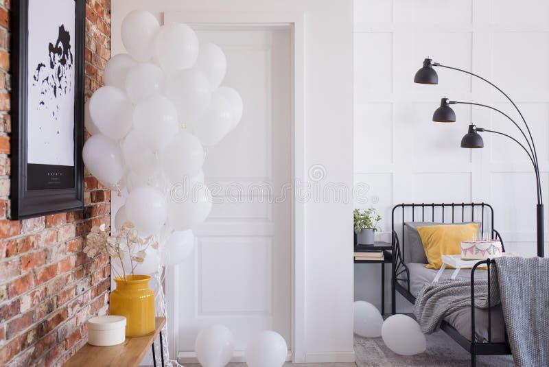 Plakat im Schlafzimmerinnenraum mit schwarzer Lampe über Bett mit orange Kissen Reales Foto stockbilder