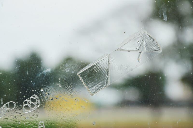 Plakbandvlek op het schild van het vensterglas en wasbel stock foto's