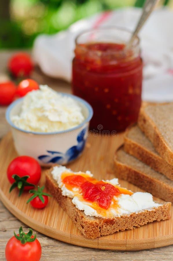 Plakken van Bruin Brood met Roomkaas en Tomaat en Chili Jam stock afbeelding