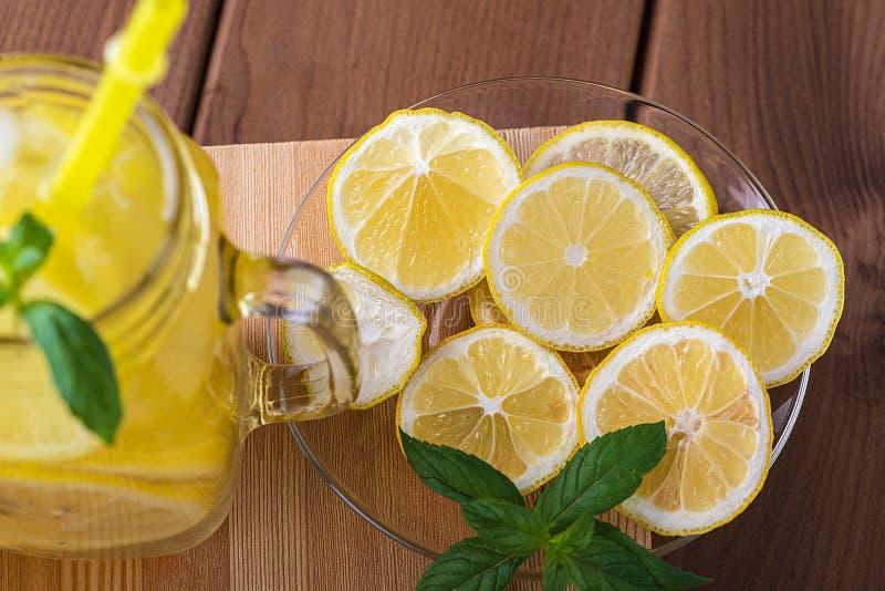 Plakken van citroen op een glasplaat en limonade op een houten lijst royalty-vrije stock afbeeldingen