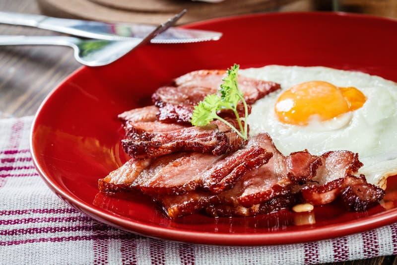 Plakken van gerookt bacon en gebraden ei op een rode plaat stock foto