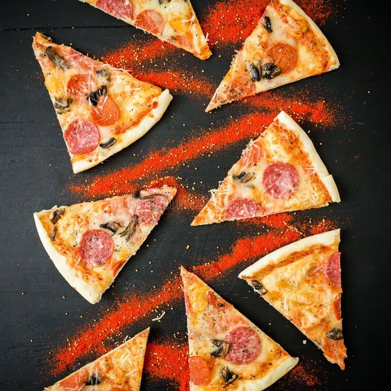 Plakken van Italiaanse pizza met salami op donkere lijst Patroon van pizzaplakken Vlak leg, hoogste mening stock afbeeldingen