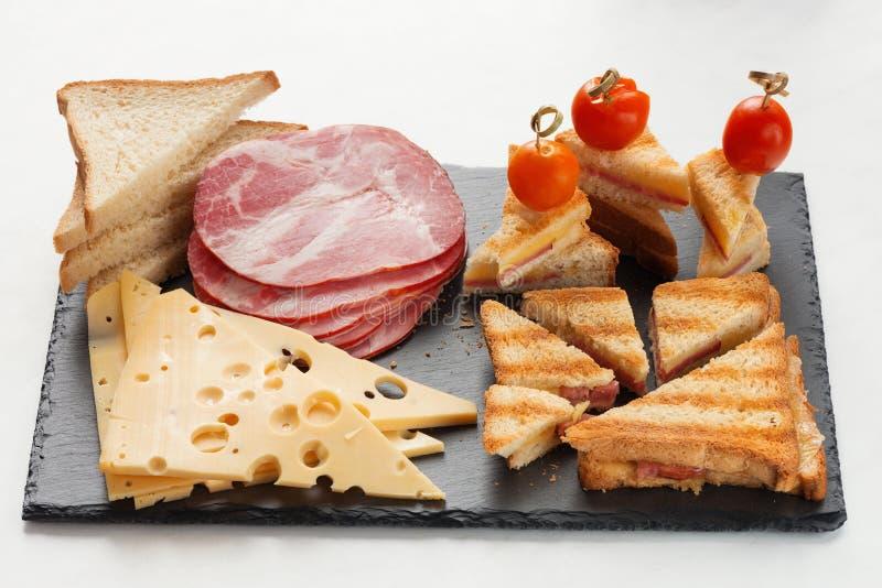 Plakken van kaas, ham, brood en de hete gemarineerde sandwiches van kersentomaten stock afbeelding