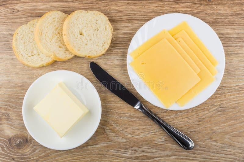 Plakken van kaas in plaat, brood, stuk van boter stock fotografie