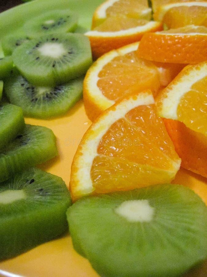 Plakken van kiwi en sinaasappel op een plaat stock fotografie