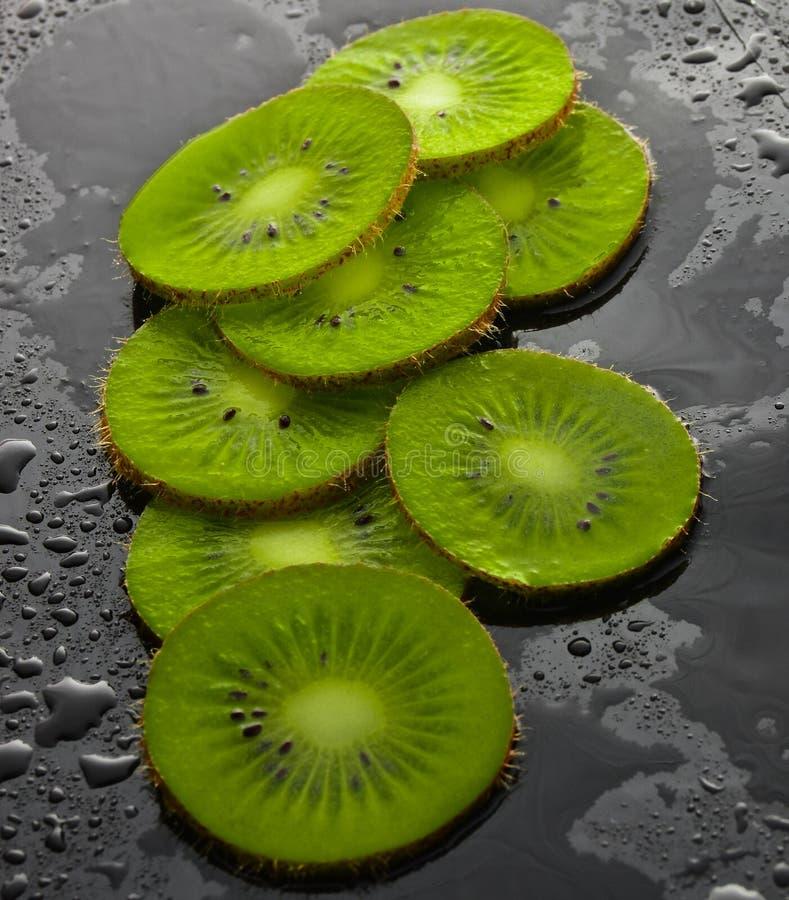 Plakken van kiwi in waterdalingen op een zwarte achtergrond Fruitconcept stock fotografie