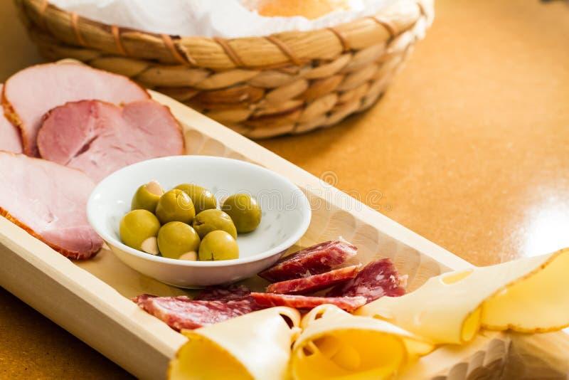 Plakken van koude vlees en olijven op een buffet royalty-vrije stock afbeelding