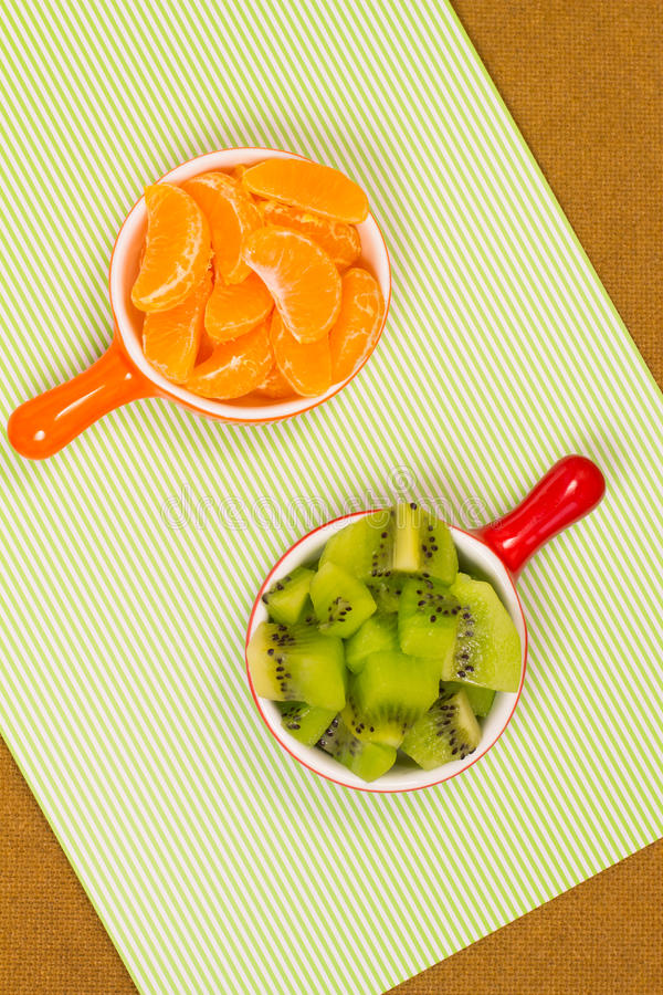Plakken van mandarijn en kiwi in een kop royalty-vrije stock afbeelding