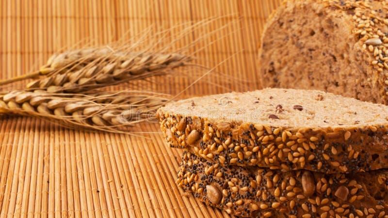 Plakken van organisch die brood met natuurlijke graangewassen op houten achtergrond en tarwe worden verfraaid royalty-vrije stock afbeelding