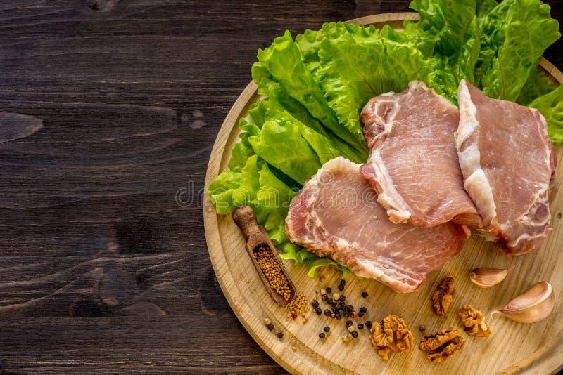 Plakken van ruw vlees Varkensvlees escalope op een houten raad stock afbeelding