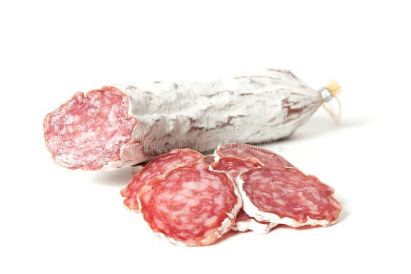 Plakken van salami op een wit wordt geïsoleerd dat stock fotografie