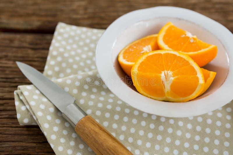 Plakken van sinaasappelen in kom op houten lijst royalty-vrije stock fotografie